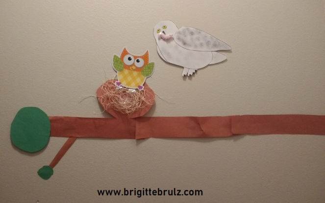 snowy owl and baby owl on limb
