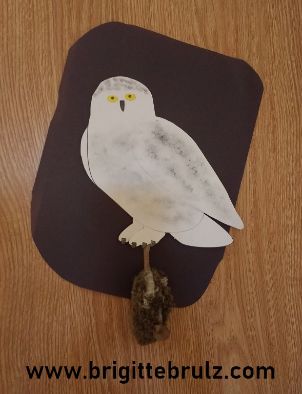 snowy owl with mouse